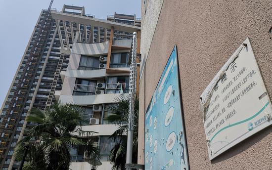 王振华旗下公司开发的楼盘一侧,墙上贴着新城物业的提示。新京报记者李云琦摄