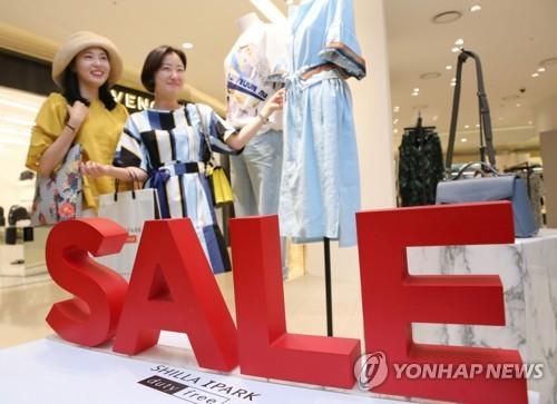 资料图片:6月14日,在位于首尔龙山区的新罗爱宝客免税店,顾客挑选衣服。(韩联社)
