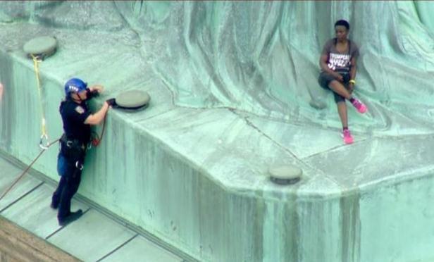 美国一女子独立日爬上自由女神像基座抗议移民政策