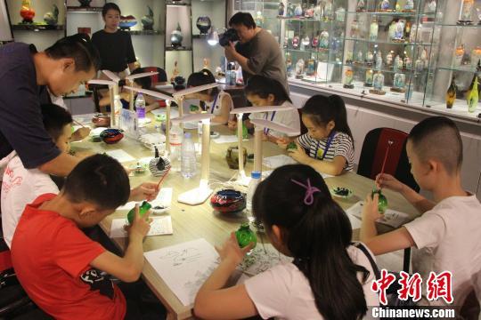 图为孩子们在中华琉璃文化创意园内,体验琉璃内画。 赵晓 摄