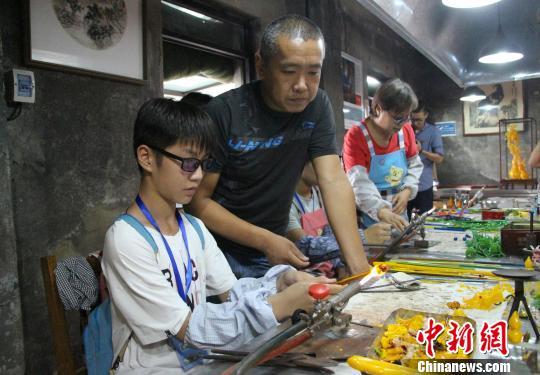在中华琉璃文化创意园内,学生们在园区老师的指点下体验琉璃加工过程。 赵晓 摄